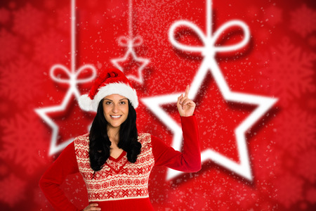 Woman pointing in the air against blurred christmas background photo