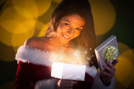 pere noel sexy: Sexy Santa don d'ouverture fille contre cercles floues de lumi�re no�l jaunes