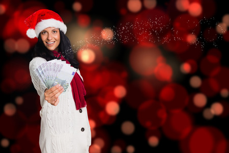 Woman holding money towards herself against blurred lights photo