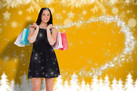 Woman walking with shopping bags against blurred fir tree background photo