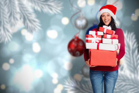 christmas scene: Woman holding many christmas presents against baubles hanging over christmas scene Stock Photo