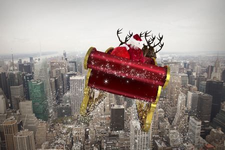 Santa flying his sleigh against city skyline Stock Photo
