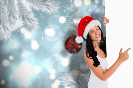 Woman pointing to large sign against baubles hanging over christmas scene photo