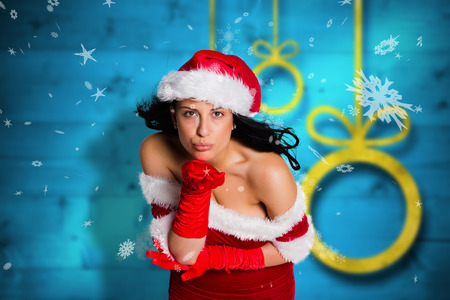Woman blowing kiss to camera against blurred christmas background photo