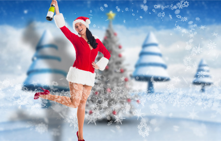 Woman smiling with champagne bottle against blurry christmas scene photo