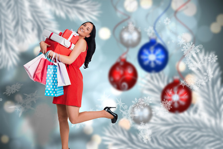 Woman standing with shopping bags against baubles hanging over christmas scene photo