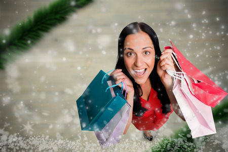 Woman standing with shopping bags against blurry christmas scene photo
