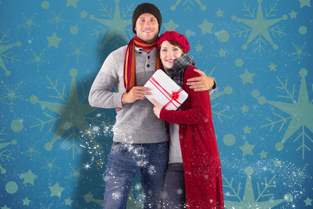 Couple smiling and holding gift against snowflake wallpaper pattern photo