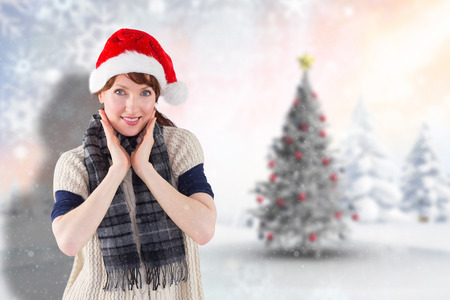 Smiling woman wearing santa hat  against blurry christmas scene photo