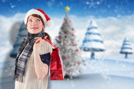 wearing santa hat: Smiling woman wearing santa hat against blurry christmas scene Stock Photo