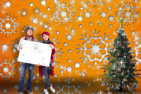 Couple holding a large sign against snowflake wallpaper pattern photo