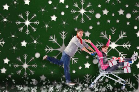 Man pushing woman in trolley against snowflake wallpaper pattern photo