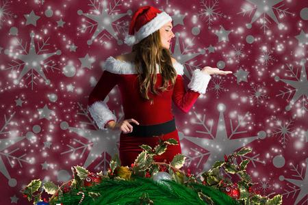 pere noel sexy: Jolie fille en costume de Santa tenue main contre motif de papier peint de flocon de neige