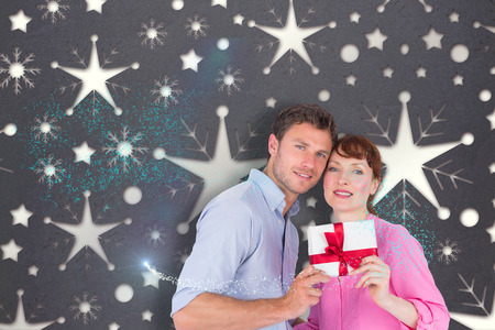 Loving couple holding a gift against snowflake wallpaper pattern photo
