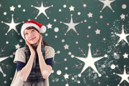 wearing santa hat: Smiling woman wearing santa hat against snowflake wallpaper pattern Stock Photo