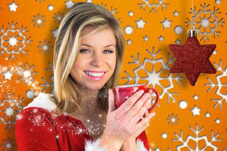 pere noel sexy: Jolie Santa fille tenant tasse contre motif de papier peint de flocon de neige Banque d'images
