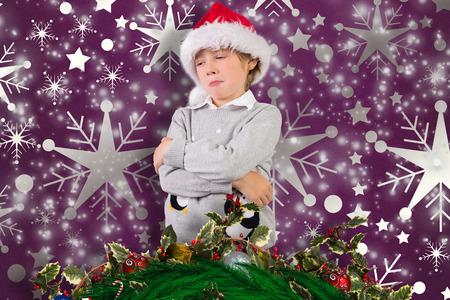 sulking: Festive boy sulking against snowflake wallpaper pattern