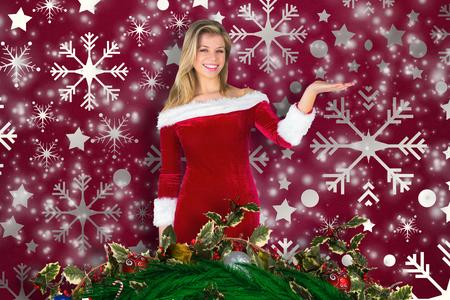 pere noel sexy: Jolie fille pr�sentant � santa tenue contre motif de papier peint de flocon de neige