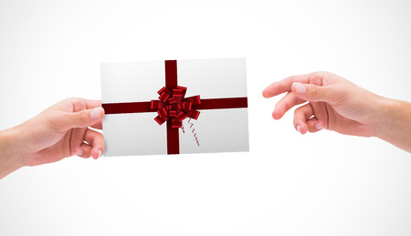 Hands holding card against red christmas bow and ribbon
