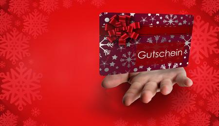 Hand bursting through paper against red snowflake design frame pattern photo