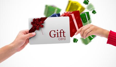 Manos que sostienen la tarjeta contra tarjeta de regalo con arco festivo
