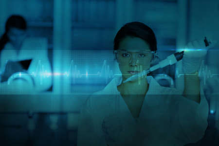 Serious chemist working with large pipette and test tube against ecg line in blue and black photo