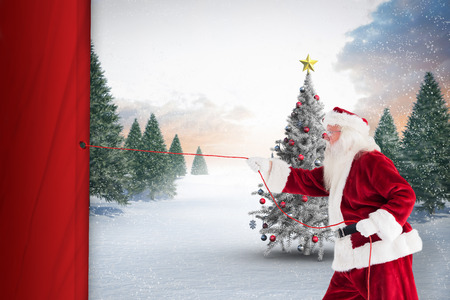 Santa pulls something with a rope against christmas tree in snowy landscape photo