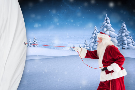 Santa pulls something with a rope against snowy landscape with fir trees photo