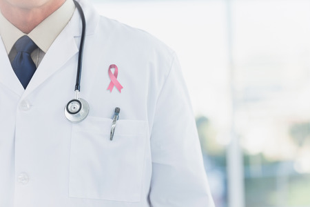 Doctor wearing lab coat wearing breast cancer awareness ribbon Stock Photo