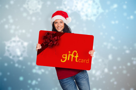 Woman holding a white sign against digitally generated delicate snowflake design photo