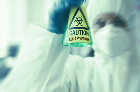 protective suit: Scientist in protective suit holding beaker with caution sticker