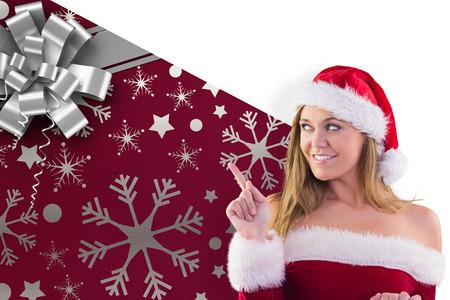 pere noel sexy: Festive blonds souriant et pointant contre no�l papier d'emballage avec l'arc Banque d'images