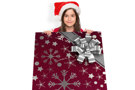 christmas wrapping paper: Festive little girl showing card against christmas wrapping paper with bow Stock Photo