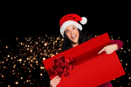 Woman pointing at sign with red christmas ribbon on black background photo
