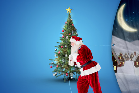 Santa claus pulling rope against cute christmas village at night photo