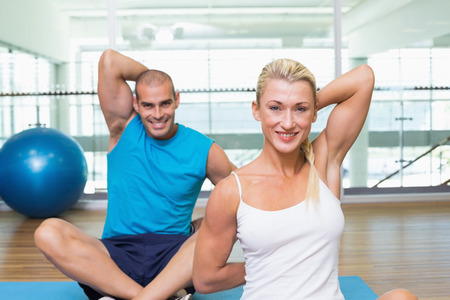 hands behind back: Portrait of happy young couple stretching hands behind back in yoga class
