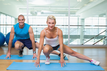 pilates studio: Portrait of a sporty young couple doing pilate exercises at fitness studio