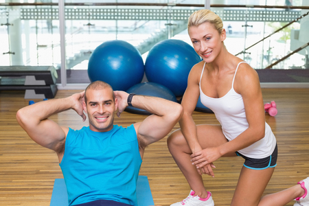 crunches: Smiling female trainer assisting young man with abdominal crunches at fitness studio