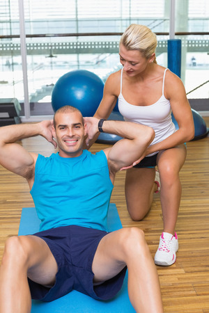 Smiling female trainer assisting young man with abdominal crunches at fitness studio photo