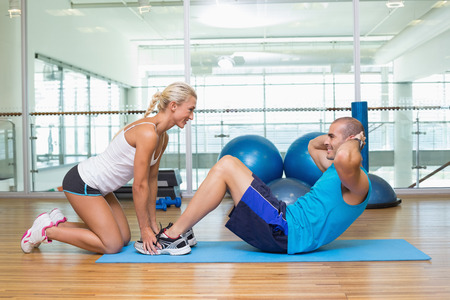 crunches: Side view of a female trainer assisting young man with abdominal crunches at fitness studio