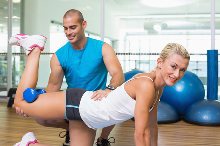Side view of a male trainer assisting woman with exercises at fitness studio photo