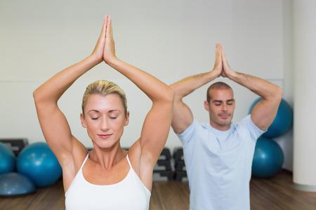 manos unidas: Pareja joven deportiva con las manos unidas y los ojos cerrados en el estudio de fitness Foto de archivo