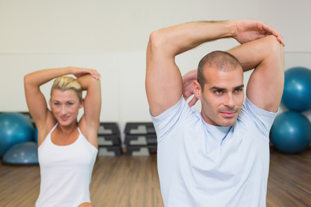 hands behind back: Portrait of young couple stretching hands behind back in yoga class Stock Photo