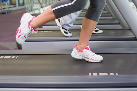 low section view: Side view low section of a fit couple running on treadmills at the gym Stock Photo