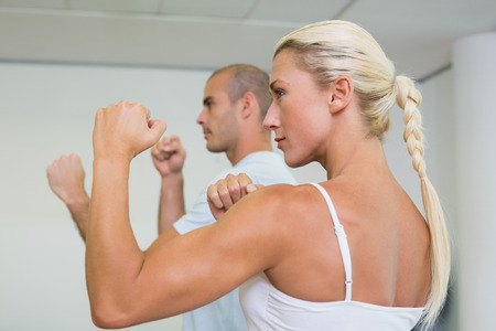 clenching fists: Side view of a sporty young couple clenching fists at fitness studio