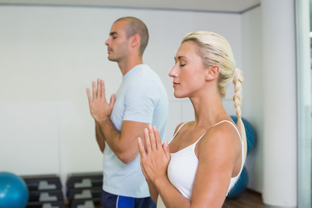 Sporty young couple with joined hands and eyes closed at fitness studio photo