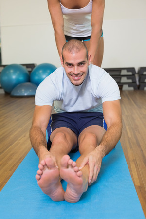 Female trainer assisting young man with stretching exercises at fitness studio photo