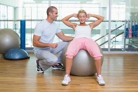 crunches: Full length of a male trainer assisting woman with abdominal crunches at the gym Stock Photo