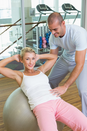crunches: Male trainer assisting woman with abdominal crunches at the gym