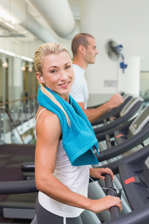 Side view of a fit young couple running on treadmills at the gym photo